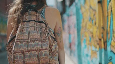 Woman with backpack walking past graffiti