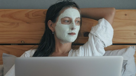 Woman with beauty facial mask lying in bed