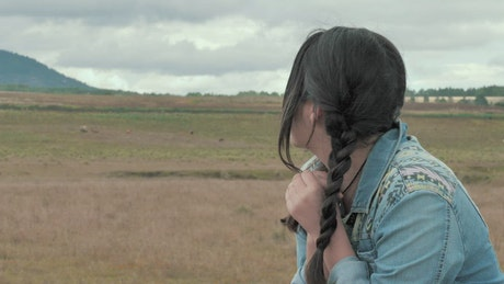 Woman with braids watching the landscape in the countryside