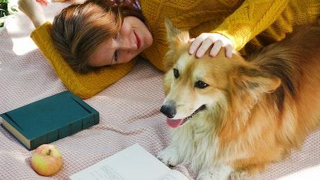 Woman with corgi dog on a picnic day