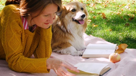 Woman with corgi dog reading in the park
