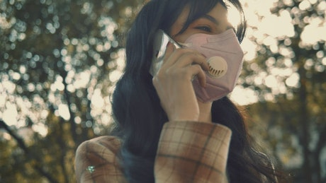 Woman with face mask talking on the phone