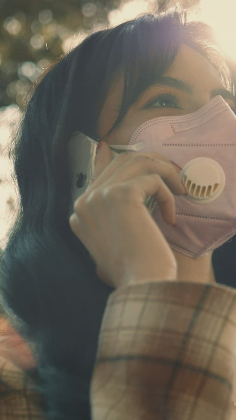 Woman with face mask talking on the phone, close up