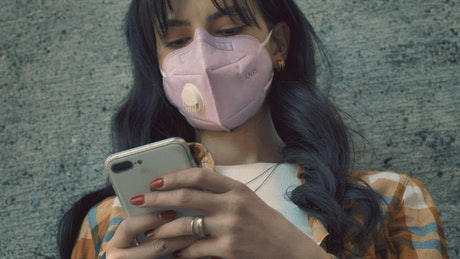 Woman with face mask texting on her smartphone