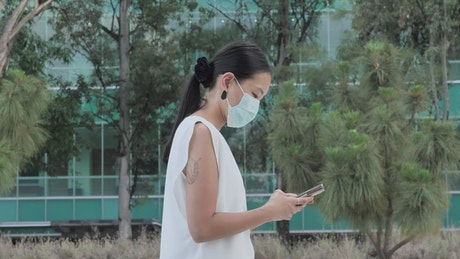 Woman with face mask walking while texting