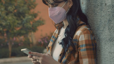 Woman with face mask while texting
