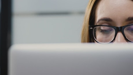 Woman with glasses working on a computer