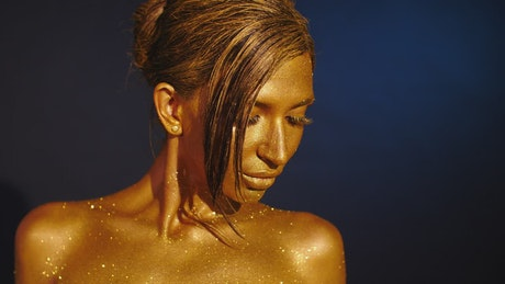 Woman with golden body paint with glitters