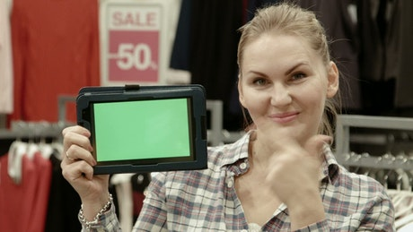 Woman with green screen tablet in clothing store