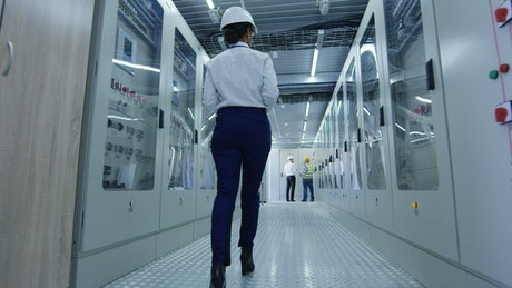 woman with helmet walking in a factory hallway