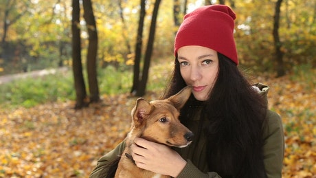 Woman with her little dog looking at the camera
