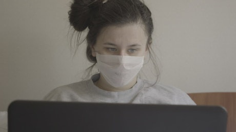 Woman with laptop in face mask sneezes