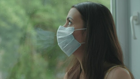 Woman with mask looking out the window