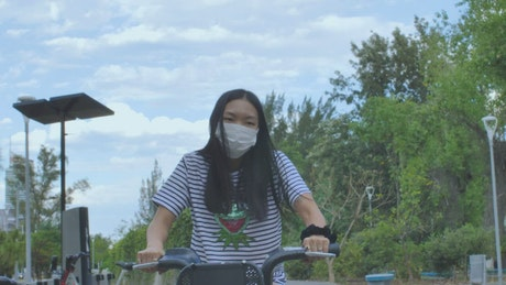 Woman with mask on bicycle in a park