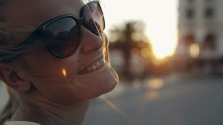 Woman with sunglasses smiling towards the camera