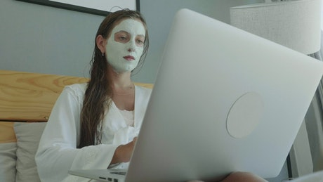 Woman working on the bed with a beauty face mask