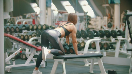 Woman working out with a dumbbell in a gym