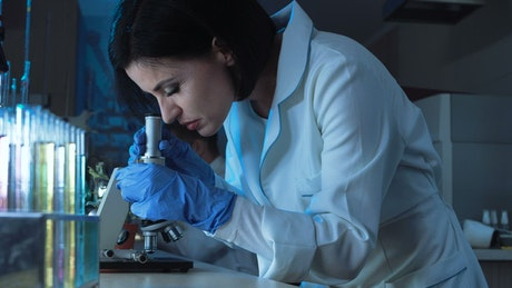 Woman working with microscope in the lab