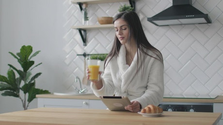 Woman works on her tablet in the morning