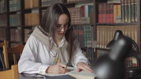 Woman writing her homework in the library
