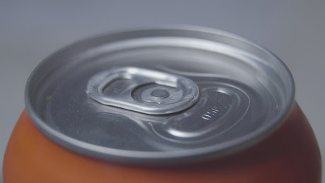 Woman's hand opening pull tab of soda can