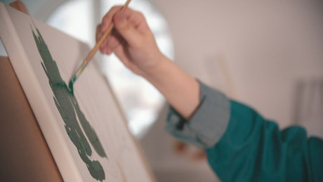 Woman's hand painting green color on canvas