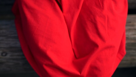 Woman's hands make heart shape on red cloth