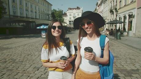Women drinking coffee walk on European street