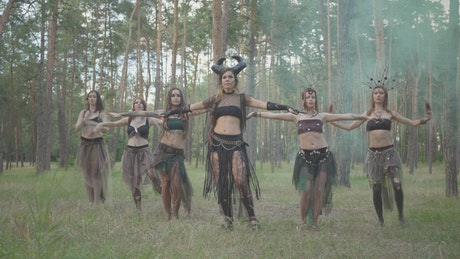 Women in gothic costumes perform dance in forest