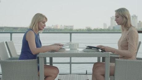Women look over menu at bayside restaurant