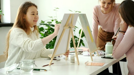 Women painting on canvas in a class