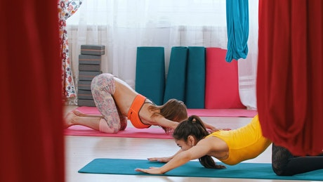 Women practicing yoga in a gym