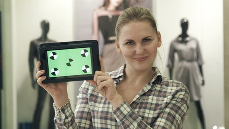Women showing a tablet with a green screen