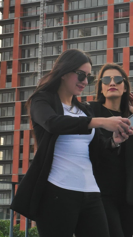 Women taking photos on a balcony