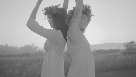 Women with wreaths of flowers dancing on a plain in black and white