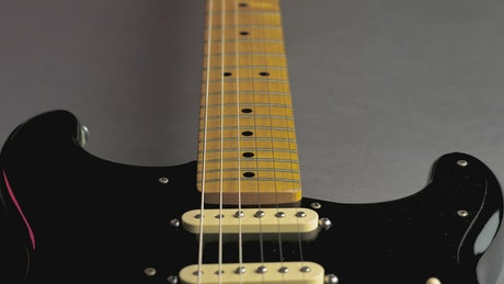 Wooden neck of a black electric guitar