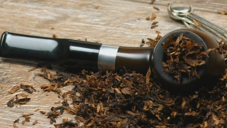 Wooden pipe surrounded by tobacco