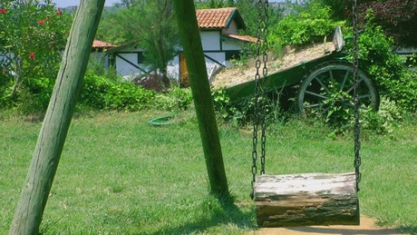 Wooden swing in the garden of a country house