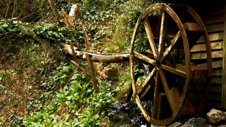 Wooden water mill in the forest