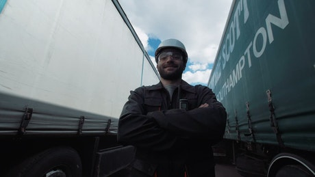 Worker between two freight trucks smiling