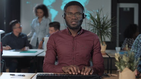 Worker in front of the computer with headset