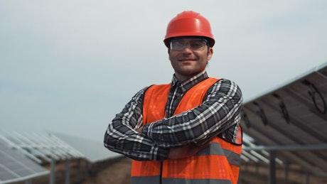 Worker posing in a solar panel field