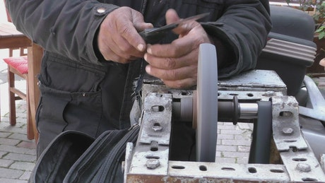 Worker sharpening his tool on a machine