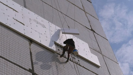 Worker suspended with ropes on a building