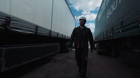 Worker walking between two freight trucks