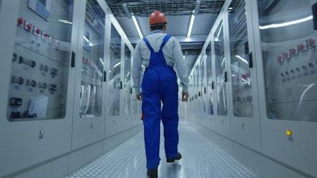 Worker walking in industrial machine corridor