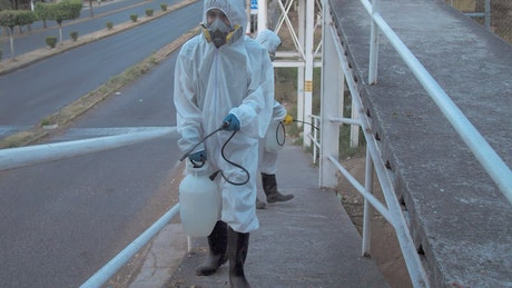 Workers in hazmat suits on a pedestrian bridge
