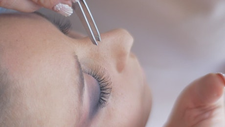 Working on a woman's eyelashes