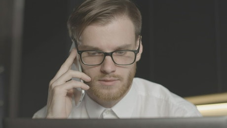 Worried man on phone call stares at laptop