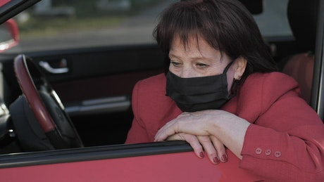 Worried old woman in her car wearing face mask